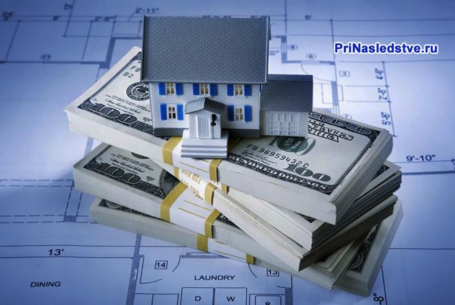 Макет дома стоит на пачке денег, план дома