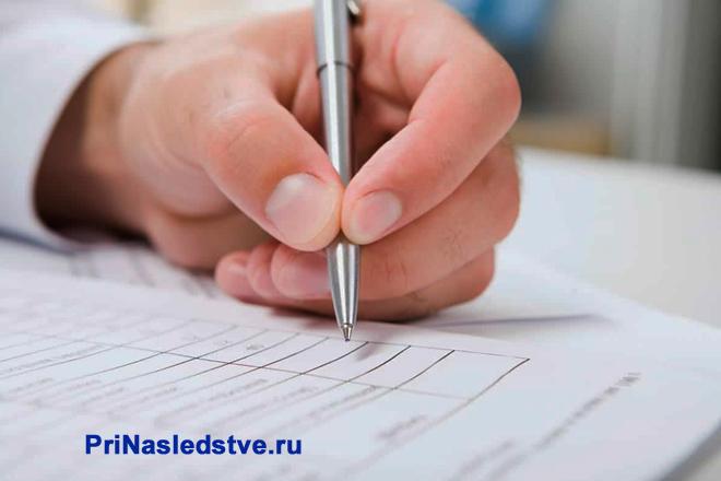 Мужчина пишет на листке бумаги