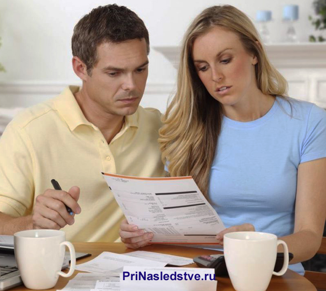 Семейная пара читает документы за кружкой чая