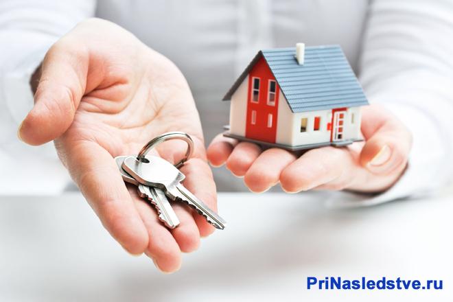 Мужчина в белой рубашке держит в руках макет частного дома и ключи