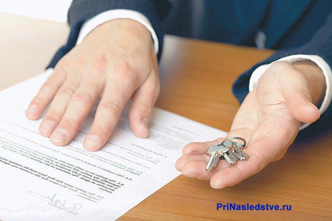 Бизнесмен держит ключи, рядом лежит договор