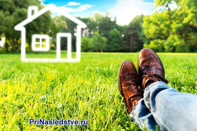 Мужчина лежит на зеленом газоне и мечтает о собственном доме