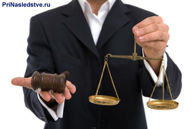 Мужчина в деловом костюме держит в руках весы Фемиды и молоточек судьи