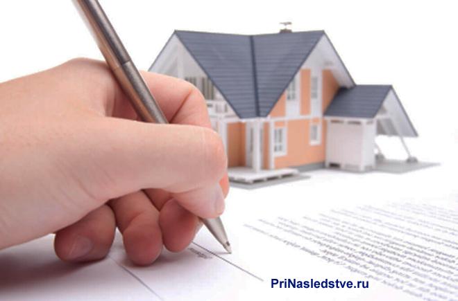Мужчина пишет ручкой на листке бумаги, рядом стоит макет частного дома