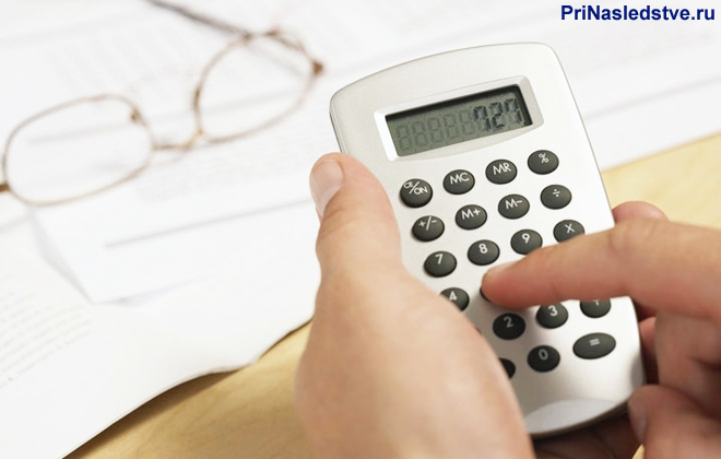 Девушка считает на калькуляторе, рядом лежат очки