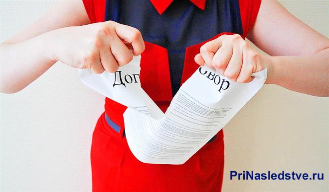 Девушка в красном платье рвет лист с договором