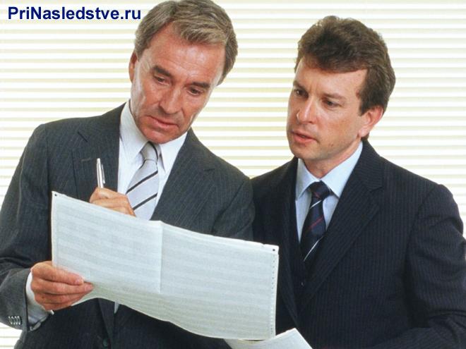 Мужчины в деловых костюмах читают записи на листах
