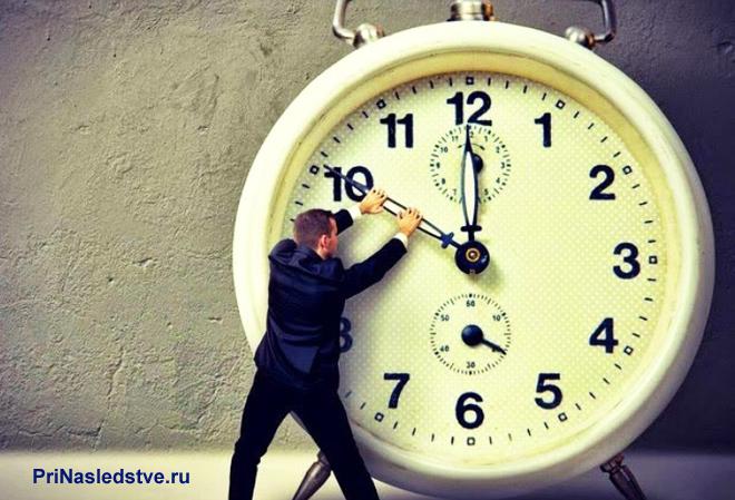 Бизнесмен двигает стрелки часов