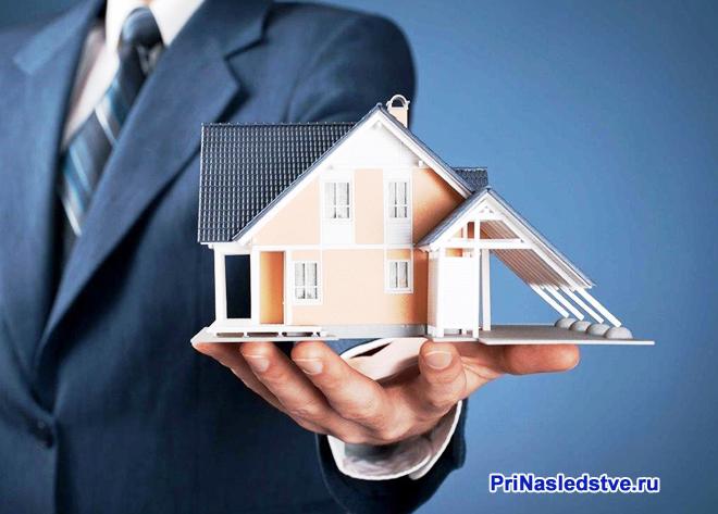 Бизнесмен держит в руке макет частного дома