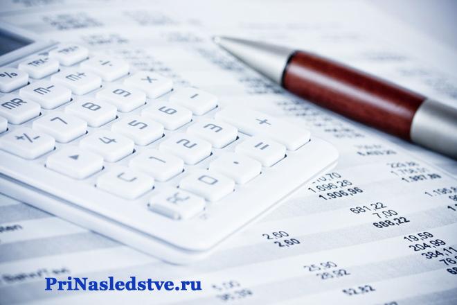 Белый калькулятор, красная ручка, бумаги