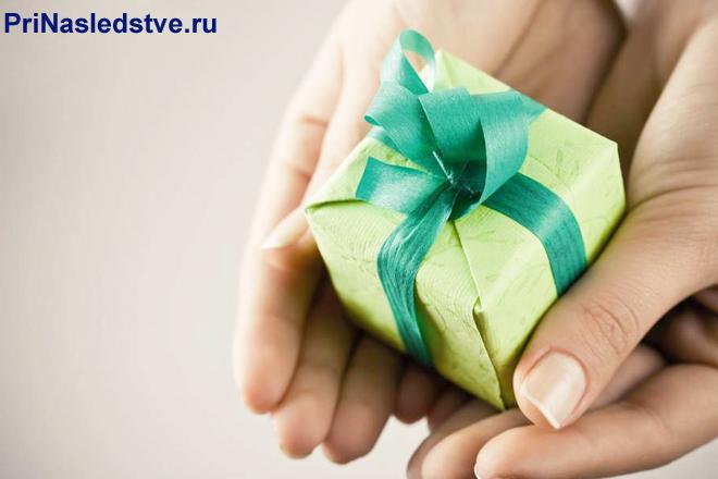 Девушка держит в руках подарок в зеленой упаковке