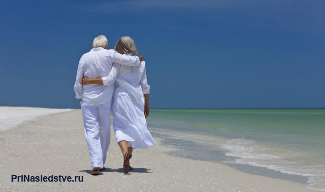 Пожилая пара прогуливается по пляжу