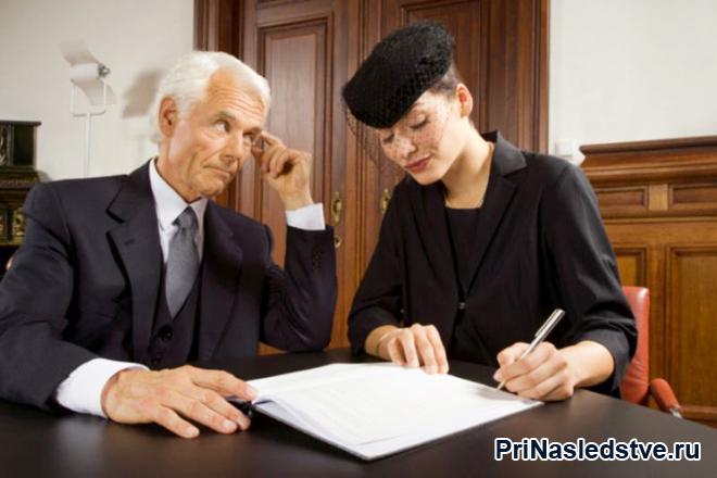 Девушка в черном подписывает документы, рядом сидит мужчина