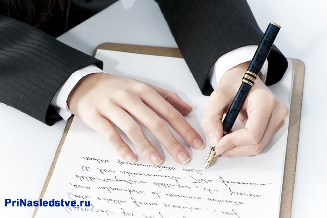 Бизнесмен пишет ручкой на листе бумаги
