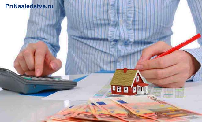 Бизнесмен считает на калькуляторе, рядом лежат деньги и стоит игрушечный домик