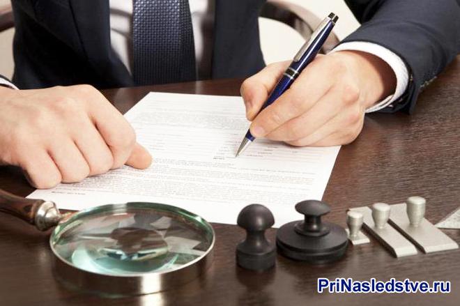 Бизнесмен сидит за своим рабочим местом, подписывает и читает документы