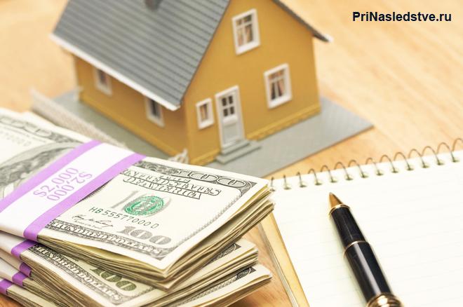 Игрушечный домик, доллары, блокнот с ручкой