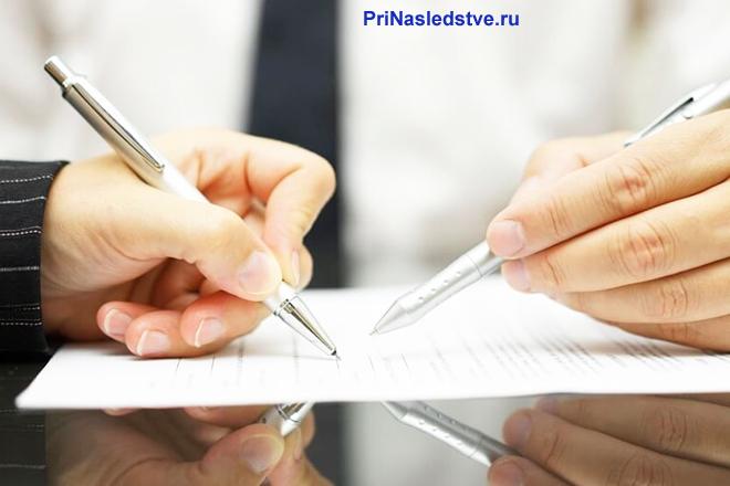 Двое мужчин сидят за столом и изучают документацию
