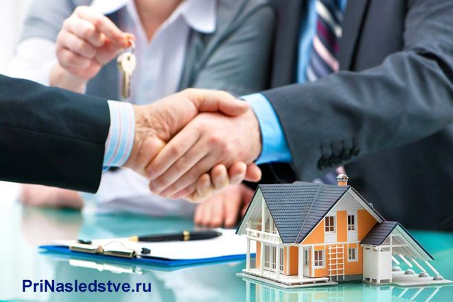 Заключение сделки за столом переговоров, рядом на столе стоит макет дома
