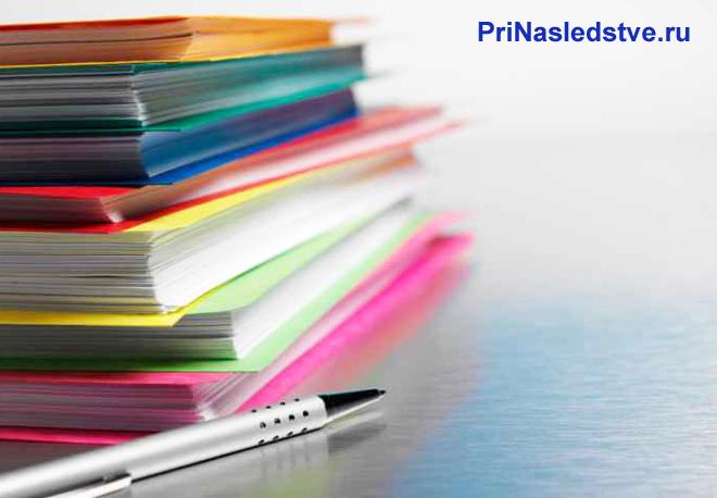 Цветные папки с документами, ручка
