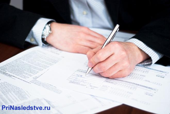 Мужчина в деловом костюме заполняет бланки документов