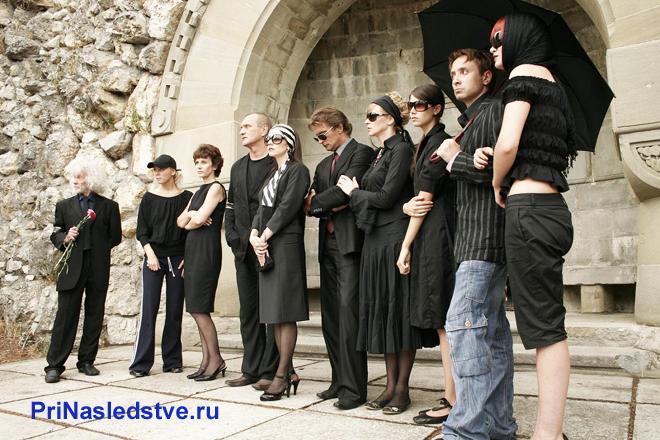 Люди в траурной одежде стоят вместе