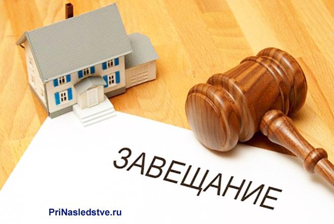 Завещание, дом, молоточек судьи лежат на столе