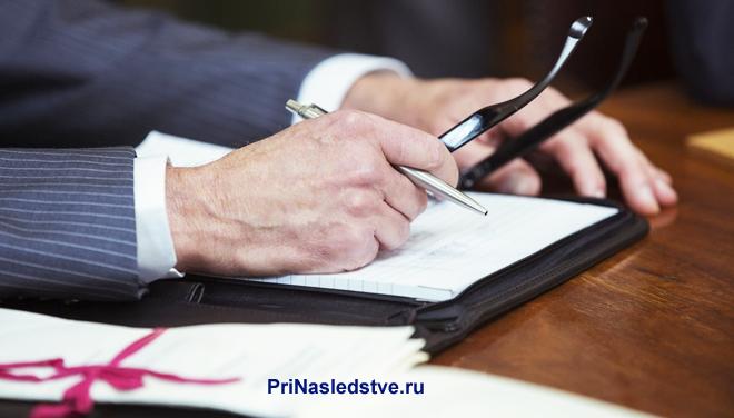Бизнесмен сидит за столом и подписывает бумаги