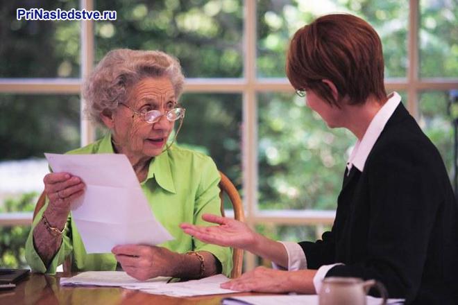 Пожилая женщина сидит за столом с листом бумаги и общается с женщиной