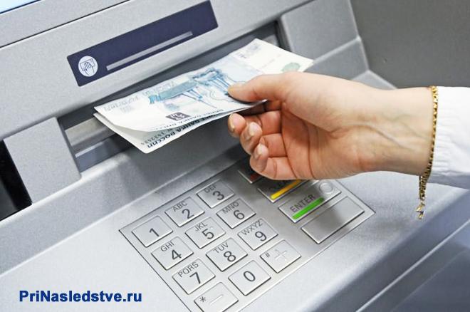 Мужчина получает деньги из банкомата