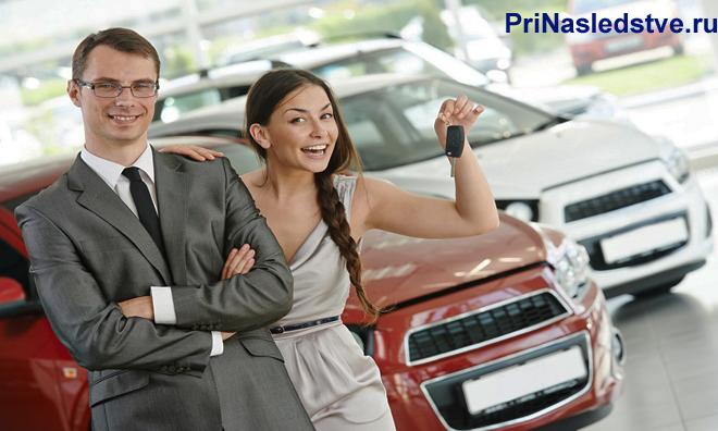 Девушка держит в руках ключи от машины, рядом стоит бизнесмен