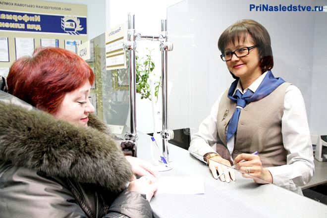 Женщина подошла к информационной стойке и разговаривает с консультантом