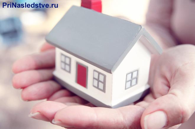 Девушка держит на ладони домик с серой крышей