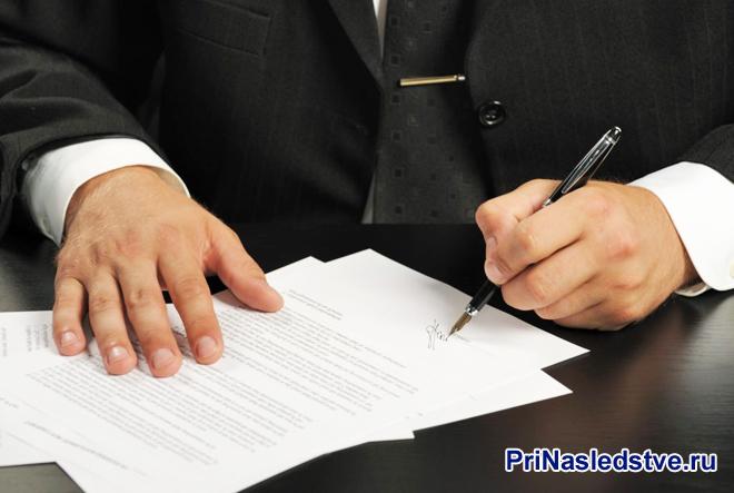 Мужчина в темном костюме подписывает контракт