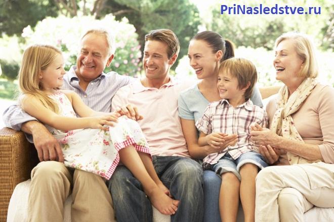 Три поколения семьи сидят на диване