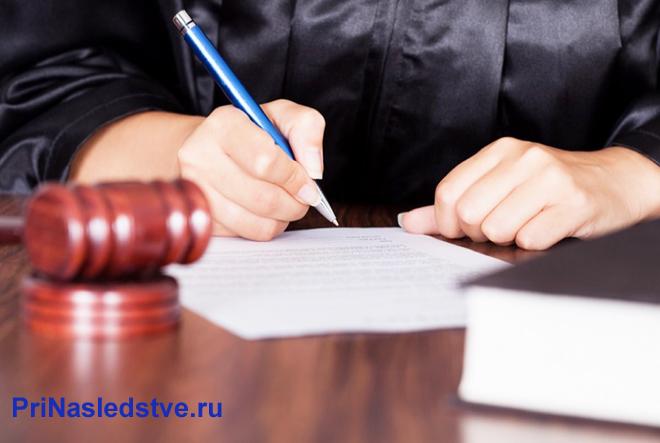 Судья подписывает документы за столом