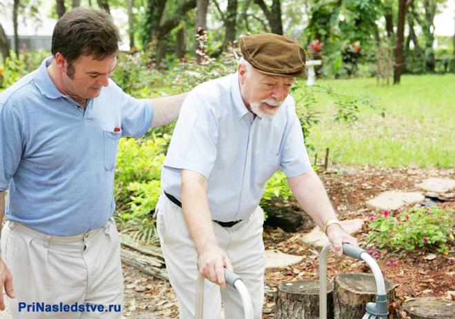 Дедушка гуляет по улице на костылях, рядом с ним идет мужчина