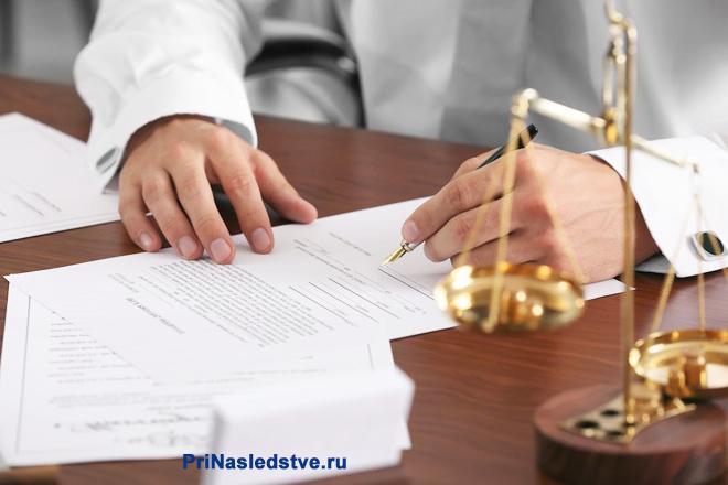 Мужчина в белой рубашке сидит за столом и подписывает документы
