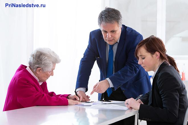 Старушка сидит за столом, читает документы, рядом с ней мужчина и женщина