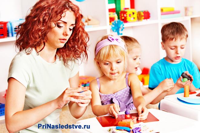 Дети и воспитательница лепят из пластилина