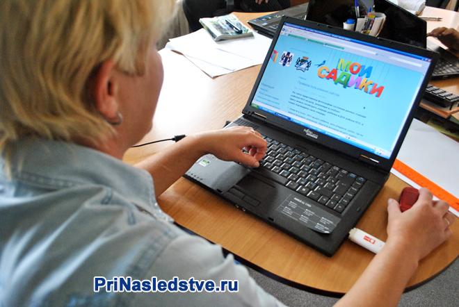 Женщина сидит за ноутбуком и смотрит сайт детского сада