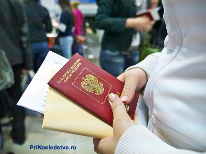Девушка стоит с паспортом в очереди