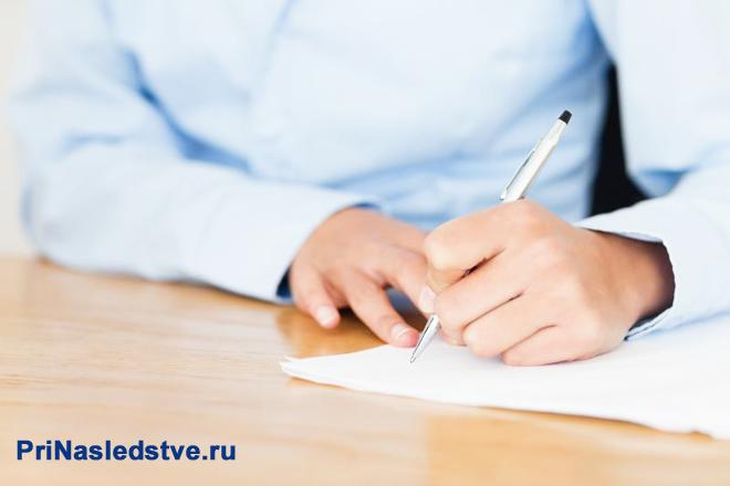 Девушка в голубой рубашке заполняет лист бумаги