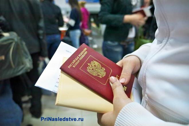 Девушка стоит со своим паспортом в руках в очереди