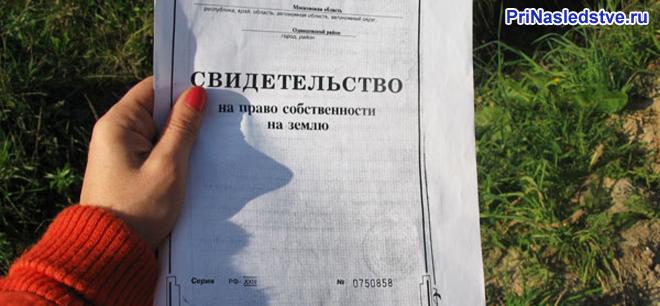 Женщина держит в руке документ на землю