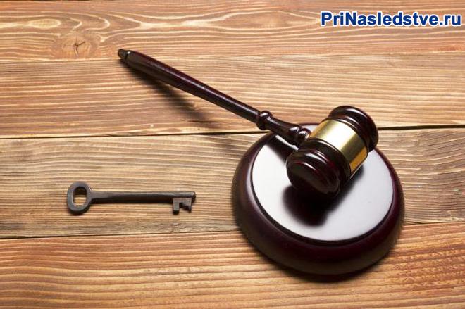Молоточек судьи, ключ лежат на деревянном столе