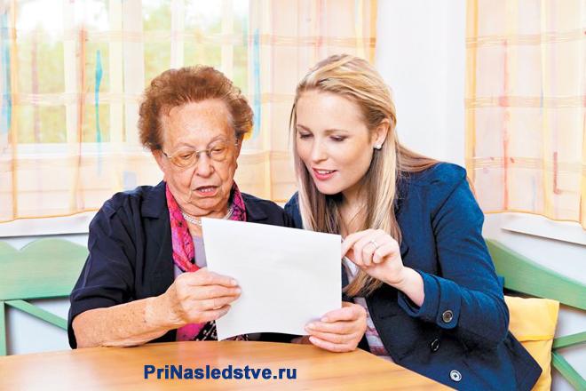 Молодая женщина и женщина в возрасте читают бумагу за столом