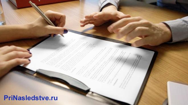 Двое людей сидят за столом и подписывают документацию