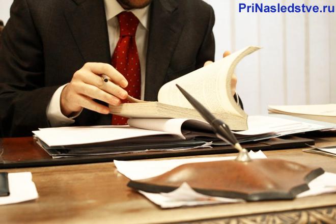 Юрист листает страницы книги за своим рабочим местом