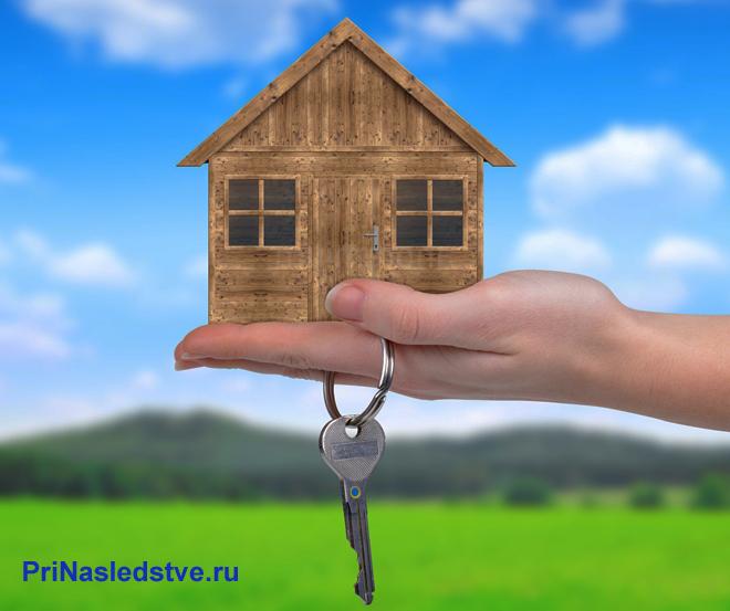 Человек держит на ладони деревянный домик и ключи